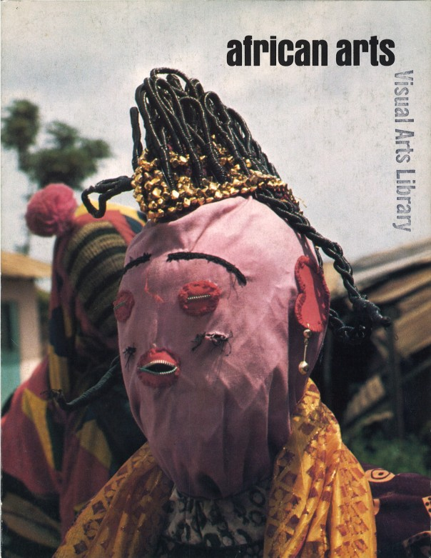 "African Arts, Volume XI, Issue Number 03. April 1978. ""The idean lyawo, described by some as reprseenting a bride or wife, who exudes quiet dignity and refinement in her dance and costume. Her body is enveloped in folds of costly fabric, and her elaborate hairstyle is bedecked with silver and gold. Iyawo's facial features are rendered in appliqued red cloth bisected by shiny zippers."" IIaro, Nigeria. Photo: Henry John Drewal."